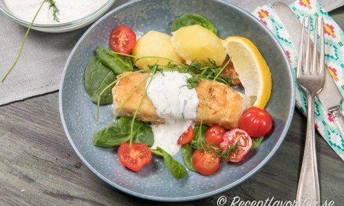Panerad torsk med gräddfilsås med dill och citron samt kokt potatis, citronklyfta, babyspenat, tomat och dillkvistar.