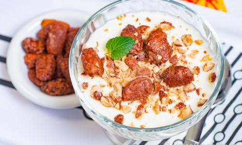 Pannacotta med citronlikör i dessert coupeglas garnerad med kanderade nötter och citronmeliss.