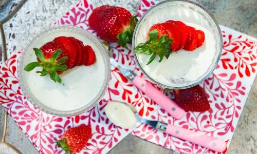 Pannacotta med matyoghurt serverad i dessert coupe-glas med färska jordgubbar.