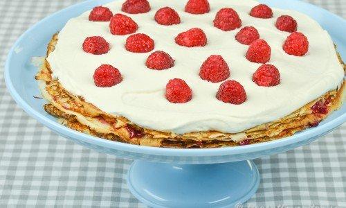 Pannkakstårta fylld med sylt och toppad med vispad grädde och färska hallon.