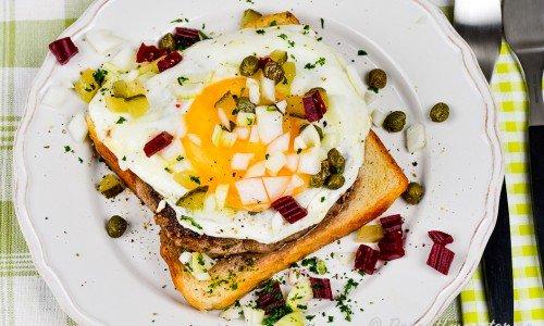 Parisersmörgås på tallrik garnerad med lök, kapris och rödbetor med mera.