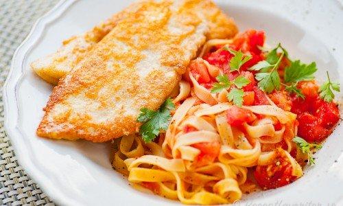 Parmesanpanerad kyckling med tomatsås och pasta på tallrik