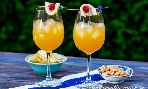 Passionfruit Punch i vinkupa med citron och marashino cocktailbär och is.