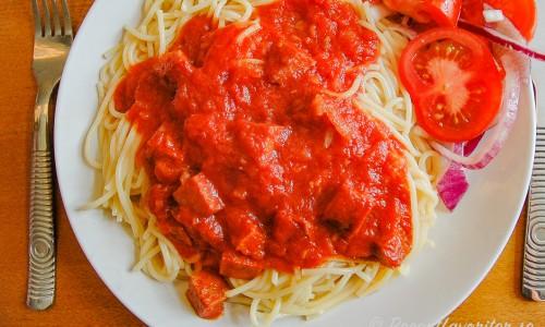 Spagetti Diablo med tomatsås och stark korv och tomatsallad på tallrik