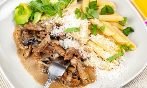Pasta med kalkon och svamp i gräddig sås på tallrik.