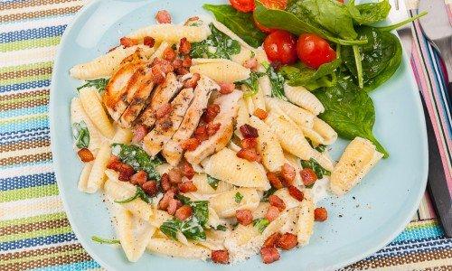 Pasta med kyckling, pancetta och spenat på tallrik