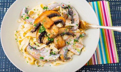 Pasta som tagliatelle serverad med krämig sås och vitlöksfrästa portabello champinjoner.