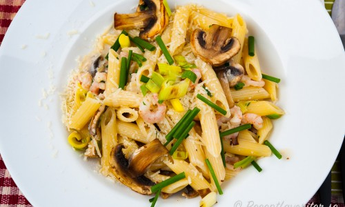 Pasta med räkor, svamp och purjolök i gräddig sås på tallrik.