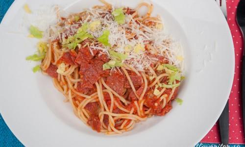 Pasta med tomatsås och salami garnerad med parmesan och hackade blad av stjälkselleri.