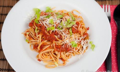 Pasta med tomatsås och soltorkade tomater garnerad med hackade blad av selleri samt riven parmesan.
