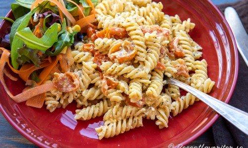 Pasta med ugnsbakad fetaost och tomater på tallrik med sallad
