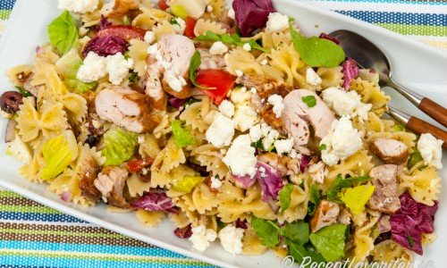 Laga en god pastasallad med farfalle pasta smaksatt med pesto och blandad med kyckling, fetaost, tomater, sallad, oliver och rödlök.