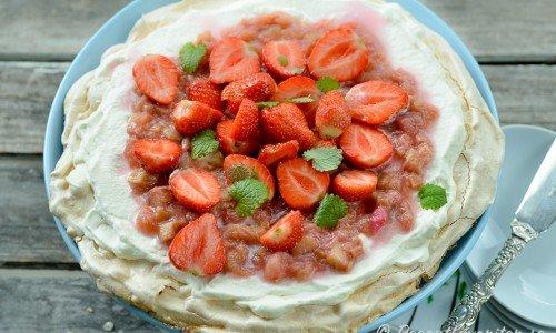 En marängtårta med grädde och smält rabarber - strimlad rabarber kokt med socker - samt färska jordgubbar.