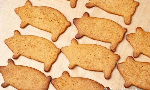 Nybakade pepparkakor i form av grisar på plåt