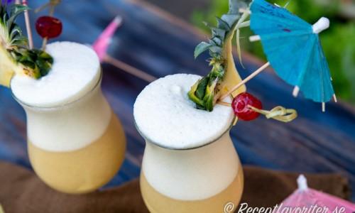 Garneringen av Piña Colada drinkarna med en bit färsk ananas med blad kvar, maraschino körsbär på tandpetare instucken i ananasen samt ett drinkparaply och sugrör.