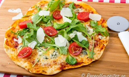 Pizza med gorgonzola på skärbräda