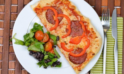 Pizza med salami och röd paprika.