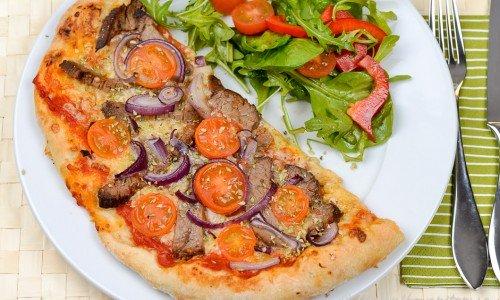 En lyxig pizza till fest med riktig skivad oxfilé, rödlök, cocktailtomater och mozarella-ost på.