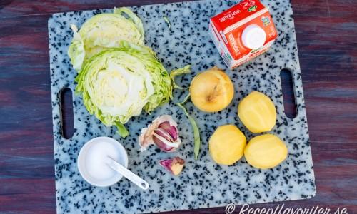 Ingredienser till potatis och vitkålsgratängen: Salt, vitkål, vitlök, gul lök, potatis och grädde.