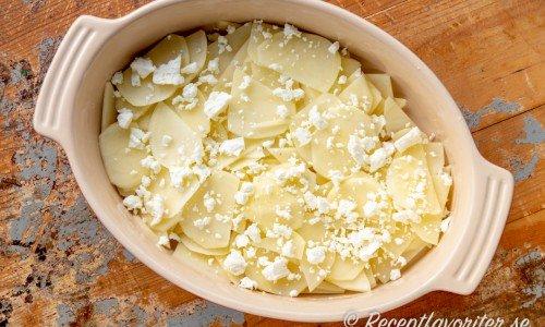 Smula en del fetaost och varva med potatisen samt toppa med resten av fetaosten.