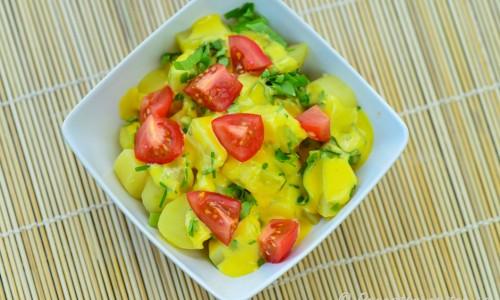 Potatissallad med vitlök garnerad med hackad persilja och tärnad tomat.