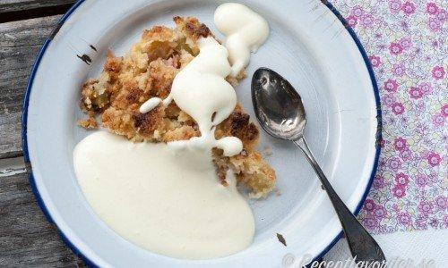 Rabarberpaj med smuldeg på tallrik med vaniljsås.