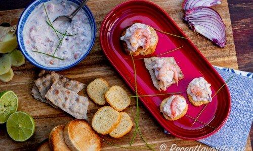 Räkröra serverad i skål till snittar av crostinis, delikatessknäcke och skivor av rostad ljus baguette.