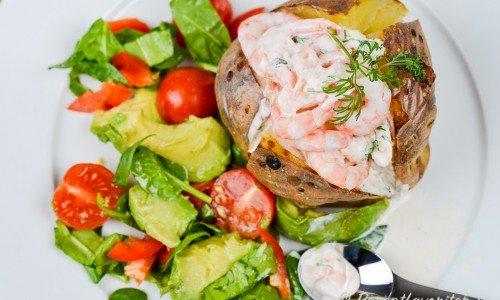 Bakad potatis fylld med räkröra med en avokado och tomatsallad till.