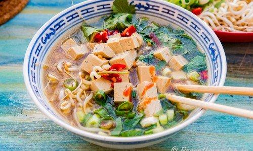 En skål ramen nudlar med tofu och grönsaker i grönsaksbuljong