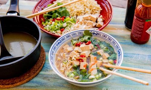 Buljong och ingredienser till soppan jämte en skål tofuramen.