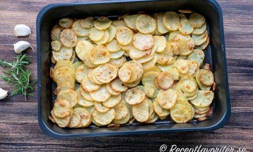 Råstekt skivad potatis med timjan, rosmarin och vitlök i form.