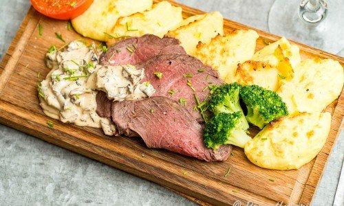 Renstek med kantarellsås, potatismos, tomat och broccoli på planka