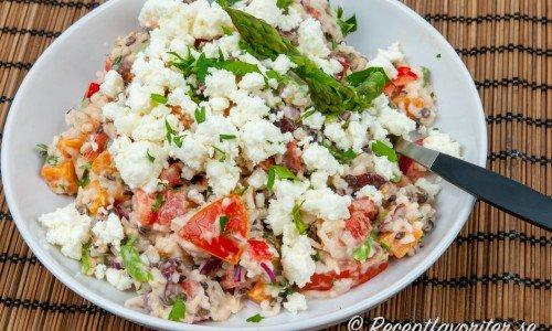 En variant på pastasallad fast med kokt kallt ris istället för pasta - här med fetaost, sparris, tomat med mera.