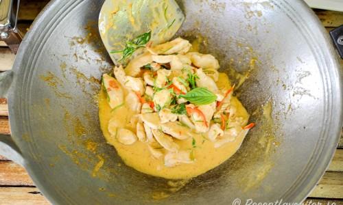 Kycklingen wokas och blandas med kokosmjölk och smaksättning i woken.