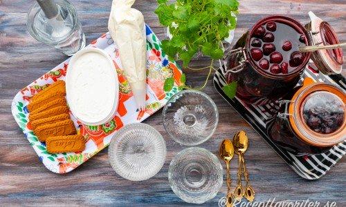 Ett serveringsförslag på romtopf med vispad grädde, vaniljglass och kex.