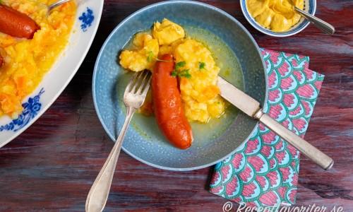 Rotmos serverat med lunchkorv, buljong och senap på tallrik