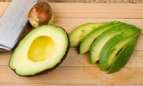 En delad avokado på skärbräda med kniv
