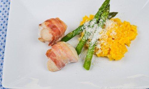 Baconlindad kyckling med saffransrisotto, sparris och riven parmesan på tallrik.