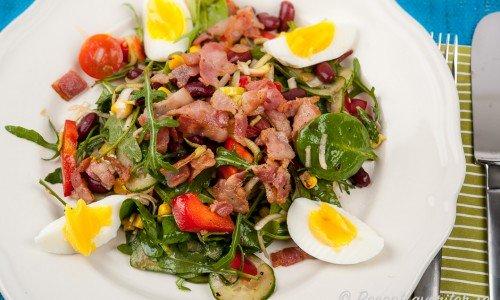 En sallad med stekt bacon, kokt ägg, grönsallad, kidneybönor, paprika, bönor, lök, majs och tomater i vinäger och olivolja smaksatt med lite chili.