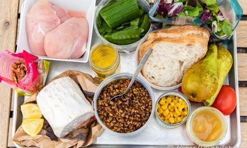 Ingredienser till salladen: kycklingfilé, valnötter, getost i rulle, citron, dressing av olivolja och äppelcidervinäger, gurka, sockerärtor, matvete, surdegsbröd, majs, grönsallad, päron, tomat och honung.