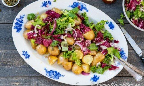 Sallad med potatis, grönsallad, kapris, rödlök och Dijondressing på fat