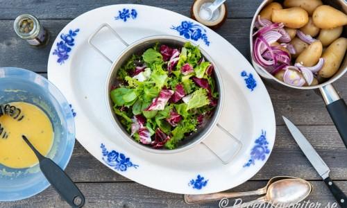 Salladsdressing, grönsallad samt kokt potatis med skivad rödlök.