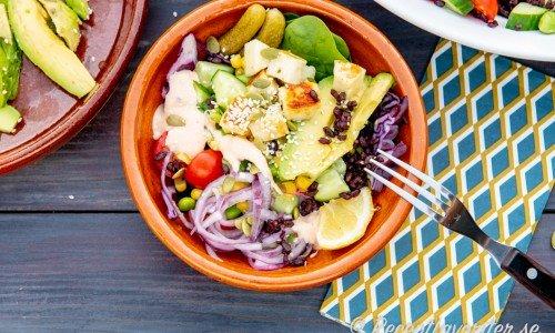 En salladskål med svart ris, halloumi och avokado samt annat grönt.