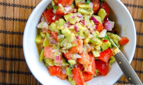 Tomat och avokadosallad eller salsa med rödlök i skål