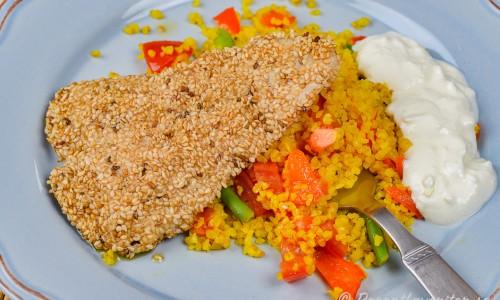 Sesampanerad kycklingfilé med couscous och kall sås på tallrik