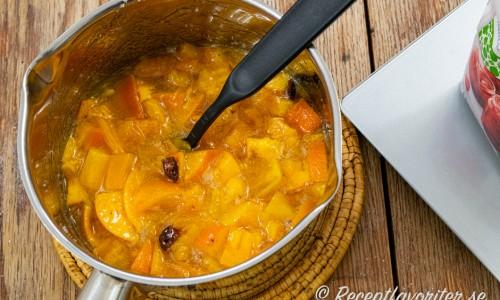 Sharonbitarna kokas till marmelad i kastrull