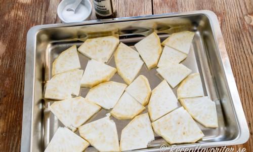 Skala och skär rotselleri i skivor på 0,5 - 1 cm samt lägg i en ugnsform.