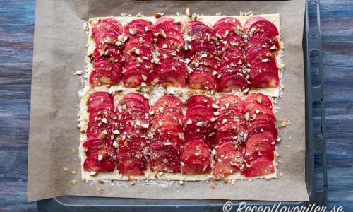 Smördegen läggs på en plåt, toppas med riven mandelmassa, skivade äpplen, socker, uppvispat ägg och hackad mandel.