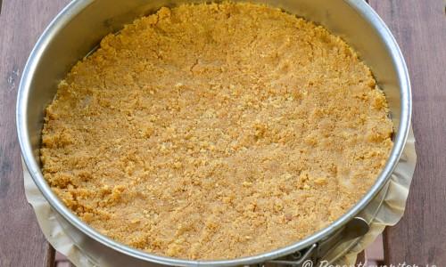 Tryck ut smulbottnen i ett jämnt lager på bakplåtspapper i en rund springform med löstagbara kanter.