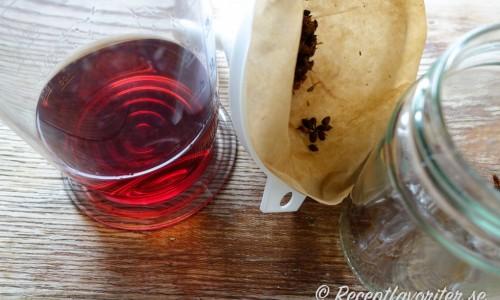 Sila av Johannesörtsblommorna i ett kaffefilter.